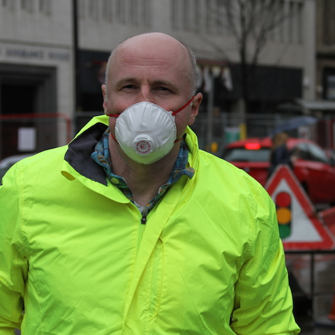 John Bridges wearing an air filter mask in front of queueing traffic on Deansgate