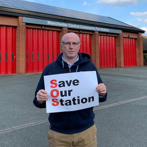 John Bridges standing outside of Manchester Central Community Fire Station holding a Save Our Station sign